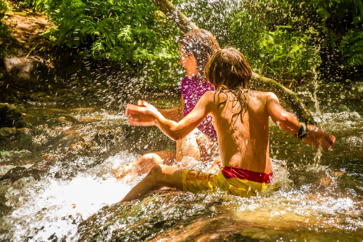 Children splashing in thermal river in forest, Kerosene Creek, Rotorua